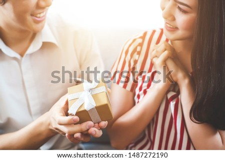 A happy couple gave his girlfriend a present. The girlfriend looked at her boyfriend's face happily, with a happy expression on her face. #1487272190