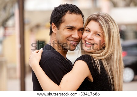 stock photo : A happy couple hugging and looking at the camera