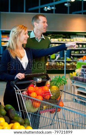 A happy couple in a supermarket buying groceries
