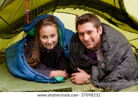 A happy couple in a tent looking at the camera