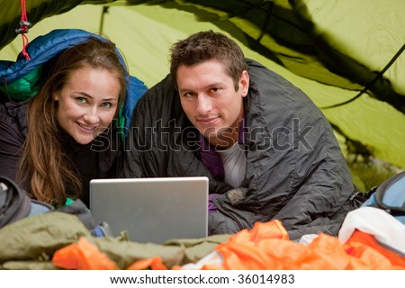 A happy couple in a tent using a computer looking at the camera