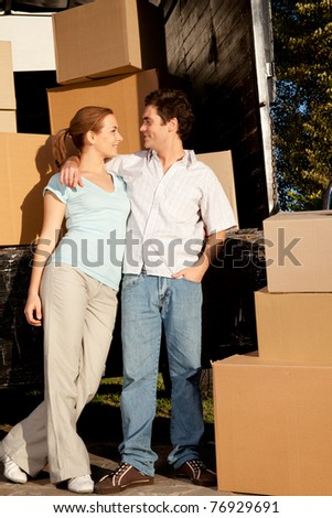 A happy couple in front of a moving van filled with cardboard boxes