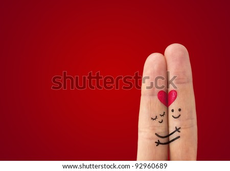 A happy couple in love with painted smiley and hugging - stock photo