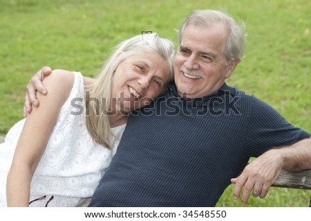 A happy couple in their early retirement years relaxes outdoors.