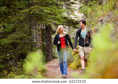 A happy couple looking at eachother and walking in the forest holding hands
