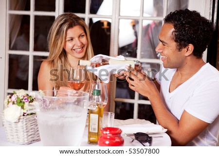 A happy couple on a date to an outdoor cafe; shallow DOF with focus on male