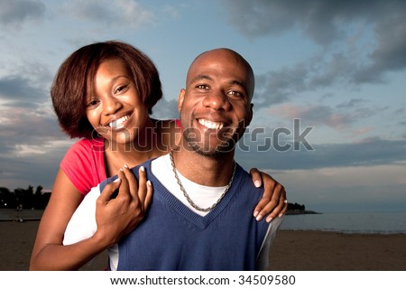a happy couple poses together at dusk