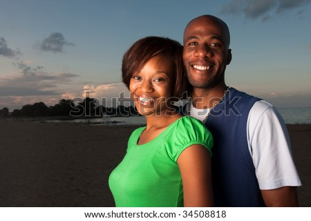 stock photo : a happy couple runs on the beach at dusk