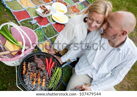A happy couple sitting close cooking food on a BBQ in the park