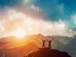 A happy couple standing together on the peak of a mountain with hands raised admiring breathtaking view at sunset
