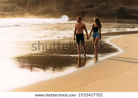 A happy couple walks along a sandy beach on the island of Bali. Couple in love at sunset by the sea. Couple in love on vacation. Honeymoon trip. Romantic couple enjoying a beach walk at sunset