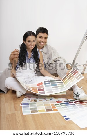 A happy couple with color samples to paint their new apartment