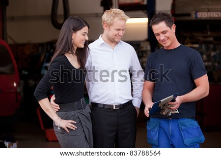 A happy customer couple receiving repair report from smiling man mechanic