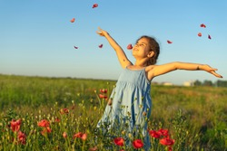 A happy cute little girl in a blue dress in a field of poppies at a summer sunset tosses the petals of wildflowers. The concept of joy of life, happiness, success