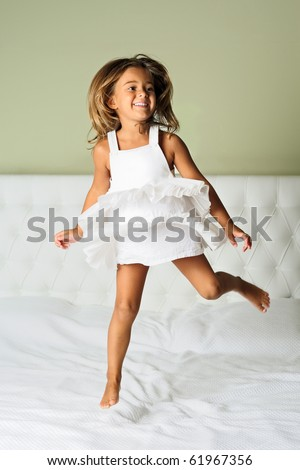 A happy cute young girl in white dress having fun jumping on bed