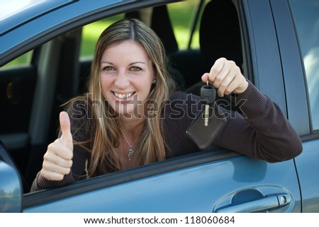 A happy driver leaning out of the window and showing the car key