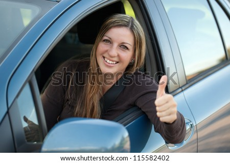 A happy driver leaning out of the window and showing thumbs up