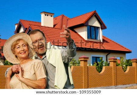 A happy elderly couple looking up at the sky standing in the road in front of a house