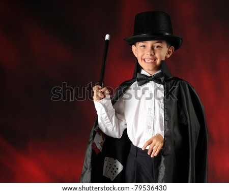 A happy elementary boy performing as a magician.  Horizontal composition with space for your text.