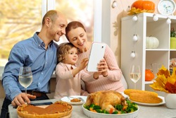 A happy family have a thanksgiving dinner and sends a video greeting to their parents on a video conference call.