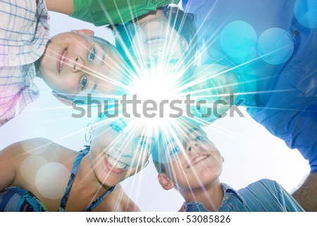 A happy family in a circular huddle formation with a bright lens flare in the center with copy space for your text or image.