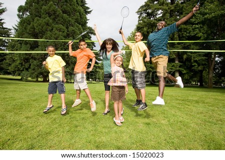 A happy family jump at the same time together, with rackets in air. - horizontally framed