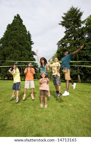 A happy family jump with each other, with rackets in air - vertically framed