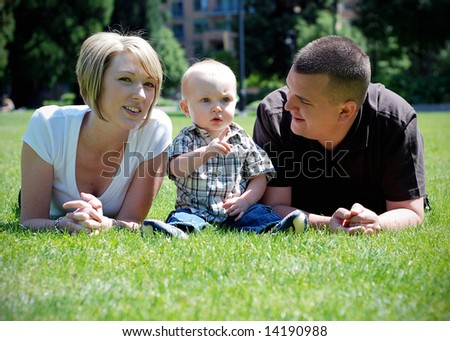 A happy family lying in the grass. The parents on the outside while their son on the inside.- horizontally framed