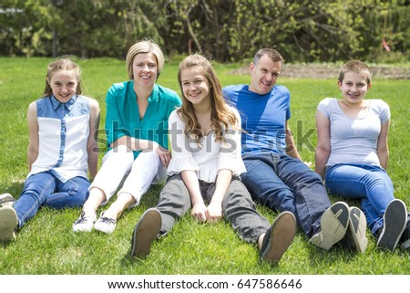 A Happy family members sitting in green grass outdoors #647586646