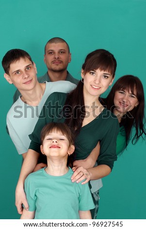 A happy family of five on a turquosi background