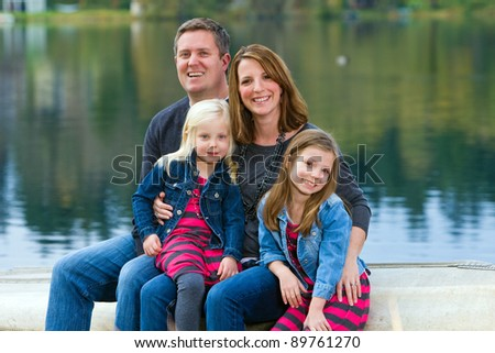 A happy family of four sitting outside in front of a beautiful lake.