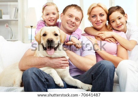 A happy family of four with a dog sitting on sofa, looking at camera and smiling - stock photo