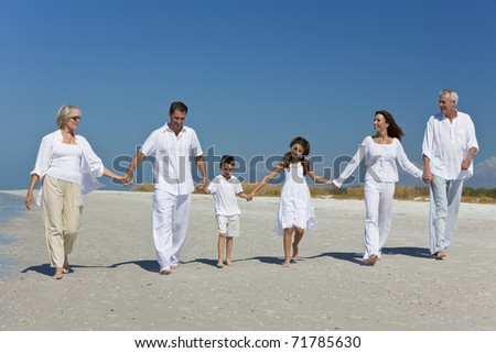 A happy family of grandparents, mother, father, two children, son and daughter, walking holding hands and having fun on a sunny beach
