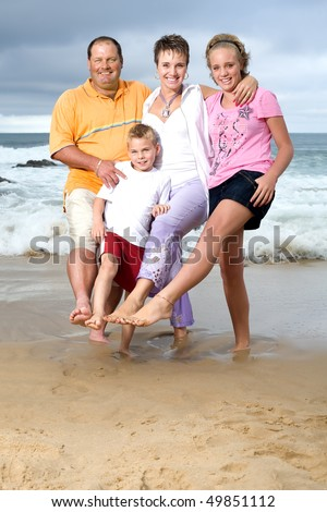 A happy family of mom, dad, sister and brother on the beach standing in wet sand with one leg and each putting their other leg together