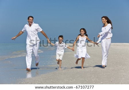 A happy family of mother, father and two children, son and daughter, running holding hands and having fun in the sand of a sunny beach