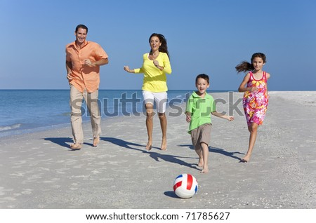 A happy family of mother, father and two children, son and daughter, running kicking a football and having fun in the sand of a sunny beach