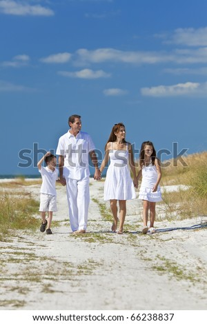 A happy family of mother, father and two children, son and daughter, walking holding hands and having fun in the sand of a sunny beach