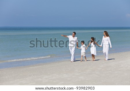 A happy family of mother, father and two children, son and daughter, walking holding hands and having fun in the sand on a sunny beach