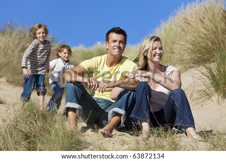 A happy family of mother, father and two sons, sitting and having fun in the sand dunes of a sunny beach - stock photo