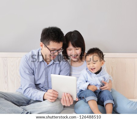 A happy, family of mother, father, son sitting on bed at home having fun using a tablet computer pc, asian people - stock photo