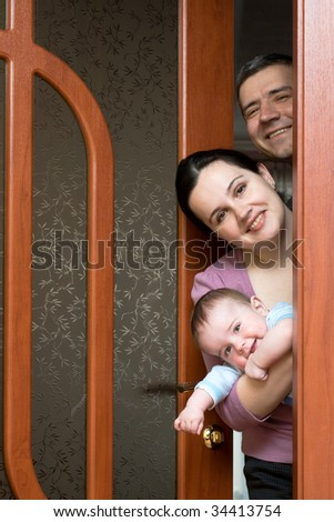 a happy family of three is looking out of the door