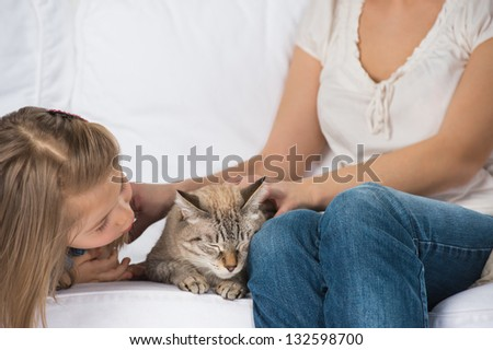 A happy family of two with a cat sitting on sofa and having fun