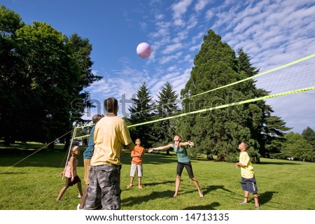 A happy family, playing volleyball together outdoors. - horizontally framed
