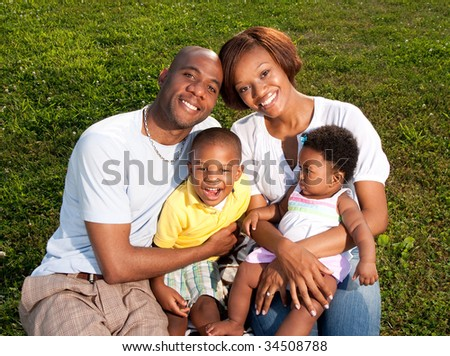 a happy family poses in a park - stock photo