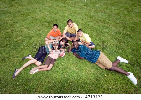 A happy family sit and lie in the grass, smiling. - horizontally framed