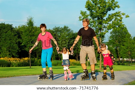 A happy family skating in a summer park