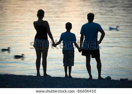 A happy family staring over the water during sunset while they hold each other hands