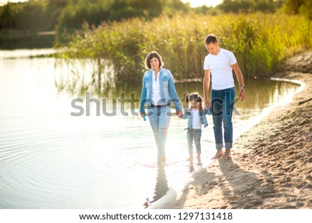 A happy family walks along the bank of the river in the evening, barefoot in the water and splashing, healthy outdoor recreation #1297131418