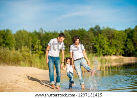 A happy family walks along the riverbank on a sunny day, will barefoot on the water and splash #1297131415