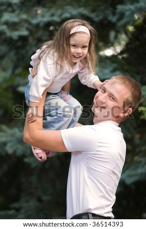 A happy father and daughter playing outside
